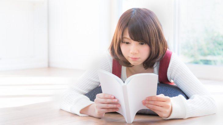 寝転んで読書する女性